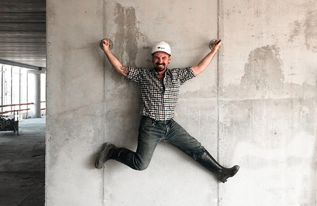 Jean-Paul Lespagnard jumping on a construction site, wearing a helmet